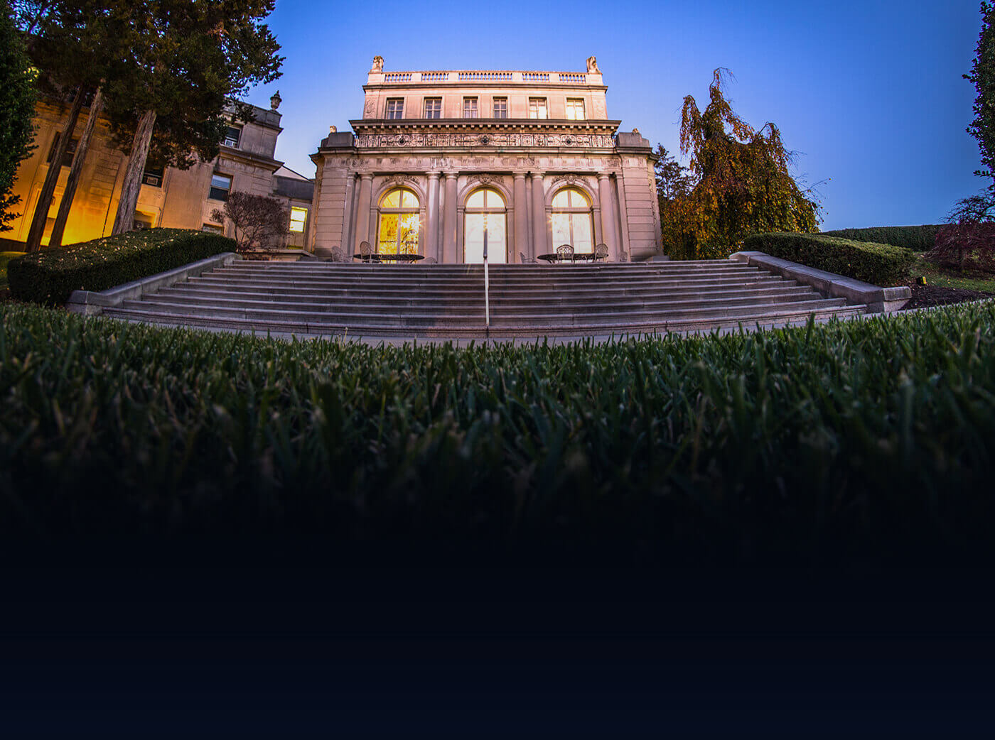 A view of the steps leading up to the historic Great Hall from the Erlanger Gardens with a rich blue sky at sunset