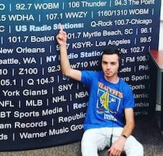 Hunter Farman pointing at the number of his radio station, 107.1--the number is printed on a poster with a variety of other radio stations.