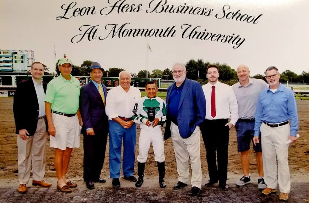A group of men standing becide a with a jockey holding an award.
