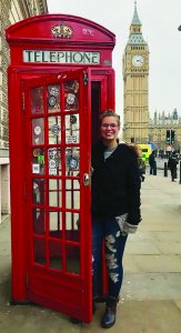 Female study abroad student poses with phone booth in England