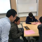 Photo shows Dr. Pang helping a student with the abacus