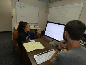 Photo shows Samantha Cavalli refining her analyses with Dr. David Darmon, Mathematics Department