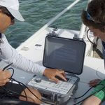 Students using a computer on a boat