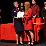 Photo shows Morgan DeWinne presenting Dr. Susan Goulding with her Induction Certificate.