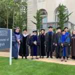 Photo of English Department faculty posing for a quick picture on their way to Graduate Commencement.