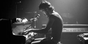 Click image to view article: Classic black and white photo of Bruce Springsteen playing the piano in concert early on in his career