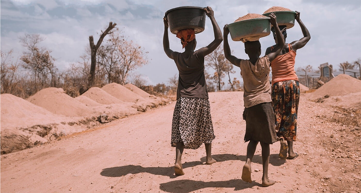 Photo of people in Africa waling along a dirt road while carrying baskets on their heads. Photo taken by Kyle Glenn - click or tap photo credit to visit web site