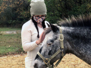 Photo of Student in Ecotherapy Program Petting a Horse