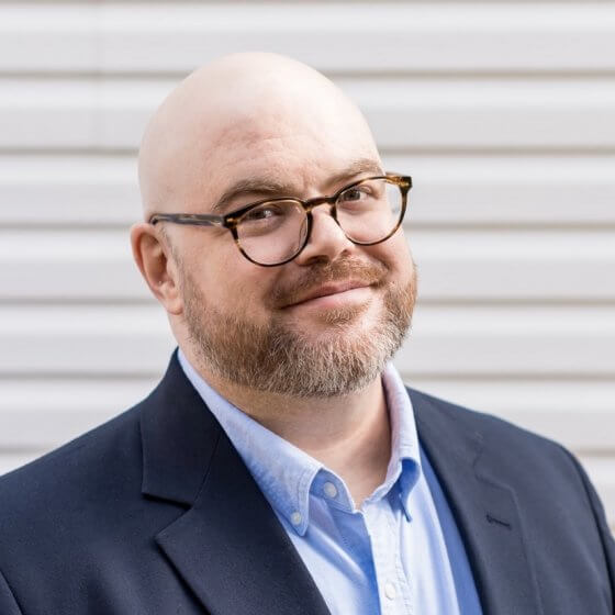 A headshot of Ryan Eckert who is wearing a light blue shirt and dark jacket, he has glasses on and a short beard.