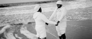 Andrew Lichtenstein photograph of two beachgoers holding each other's hands near a calm surf