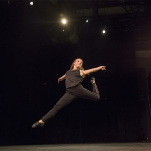 A woman in mid leap duing a dance