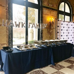 The words Hawk Family spelt in balloons shaped like letters hanging above table with catered food.