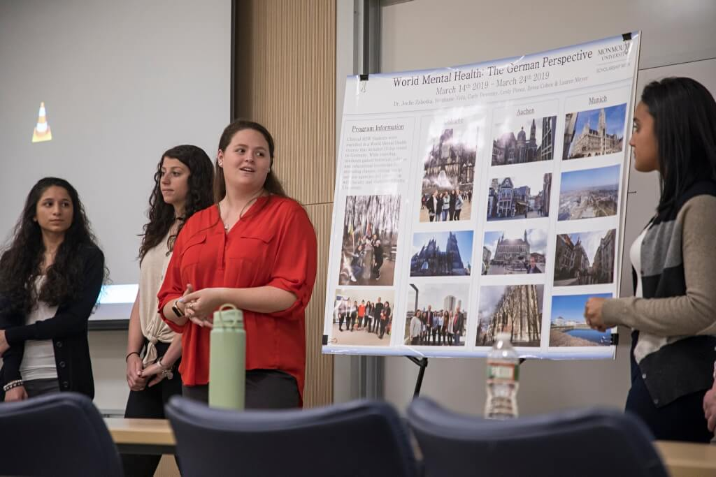 Four students speaking by a clipboard titled 'World Mental Health: The German Perspective' with photos showcasing different locations in Germany.