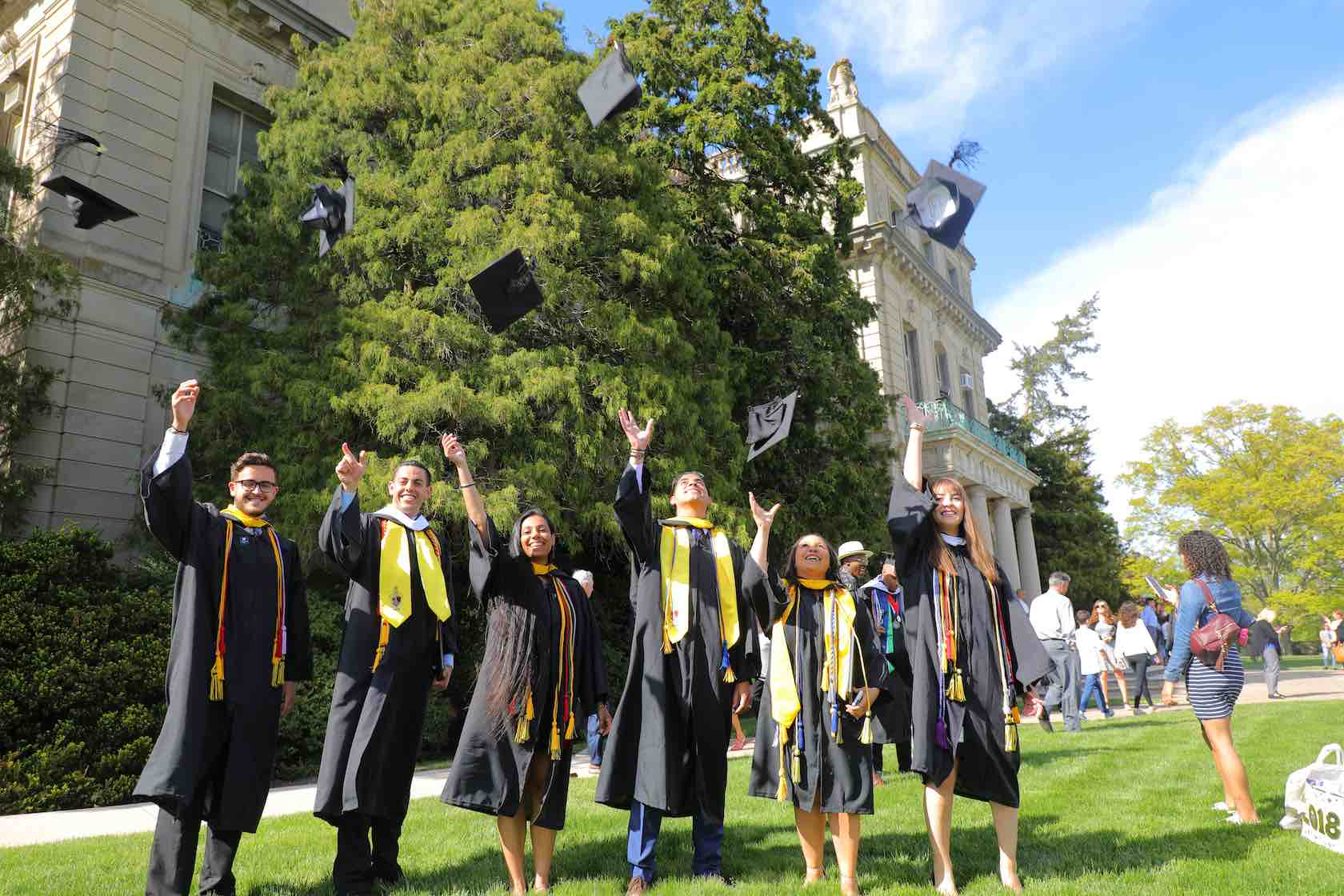 Photo of Monmouth University Graduating Students Throwing Mortarboards in the Air