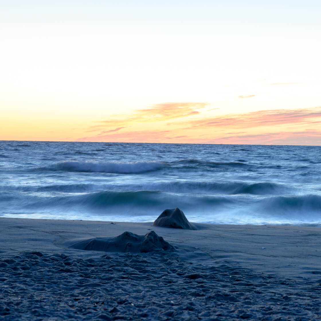 photo of a sunset, with mild waves crashing on a beach