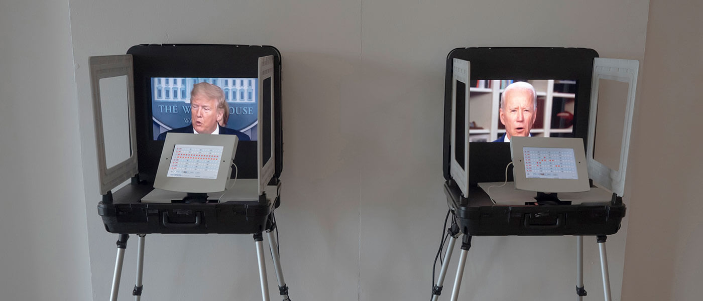 Photo shows two laptop computers each on separate chairs. the left screen shows Donald Trump talking while the right screen shows Joe Biden.