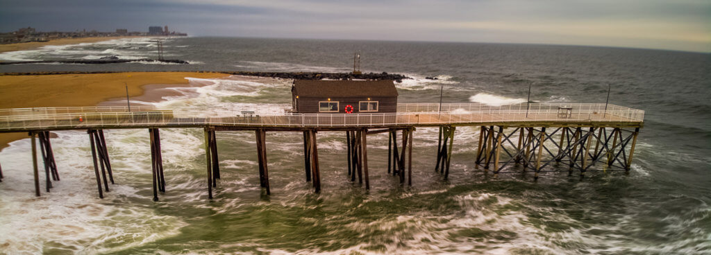 Photo shows a pier jutting into the ocean along the Jersey shore
