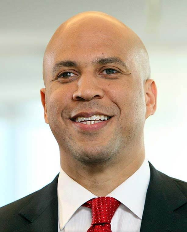 a headshot of Senator Cory Booker, who is wearing a black suit with a white shirt and red tie