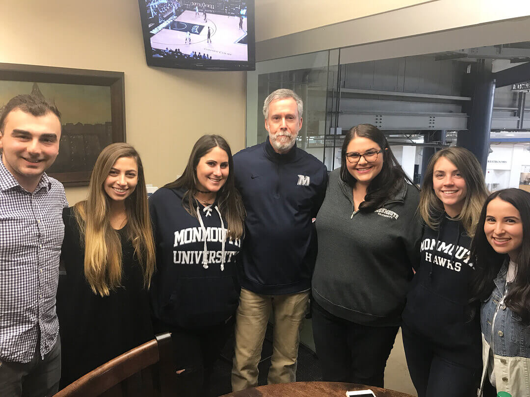 A shot of students posing alongside Grey J. Dimenna, president of Monmouth University