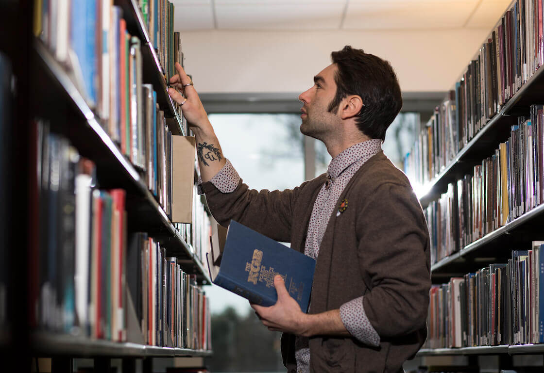 A student sifting through a collection of books on one the shelves of the Library