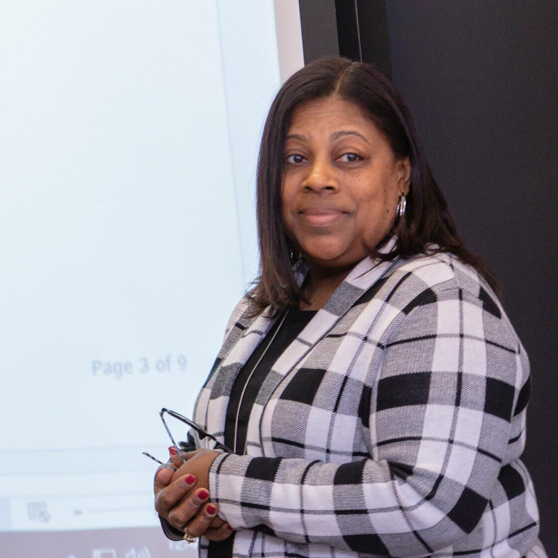 Professor Lavetta Ross teaching near a projector