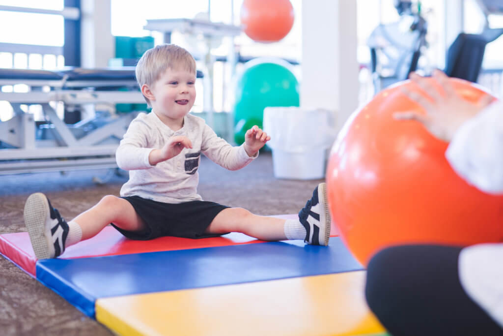 Photo of young child on exercise mat during therapy session
