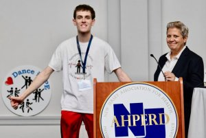 Photo shows Brad Comer at podium with NJAHPERD past President Laurie Cancalosi during an event.
