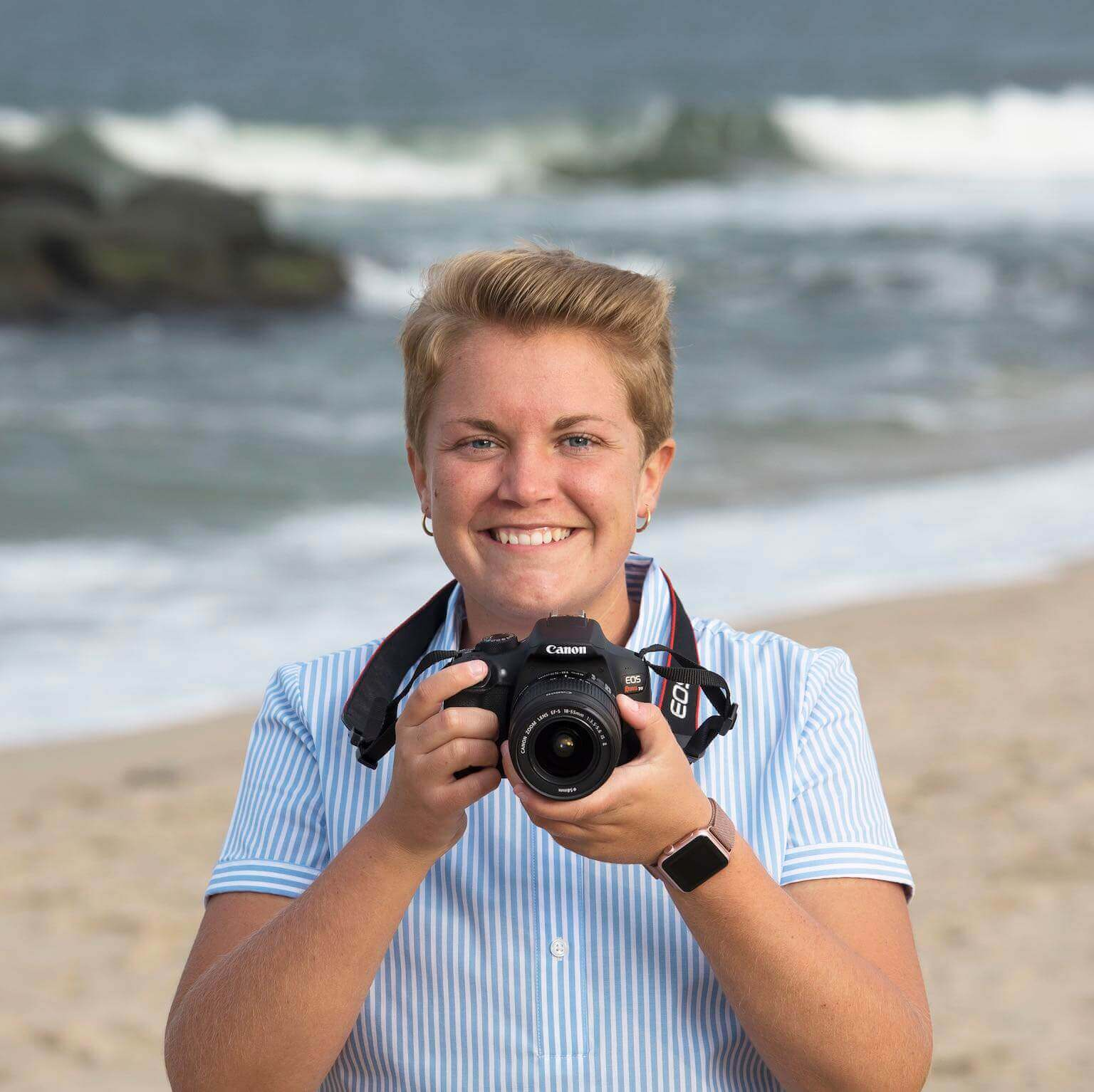 Emily Blaser holding a Canon camera with the Ocean behind her.