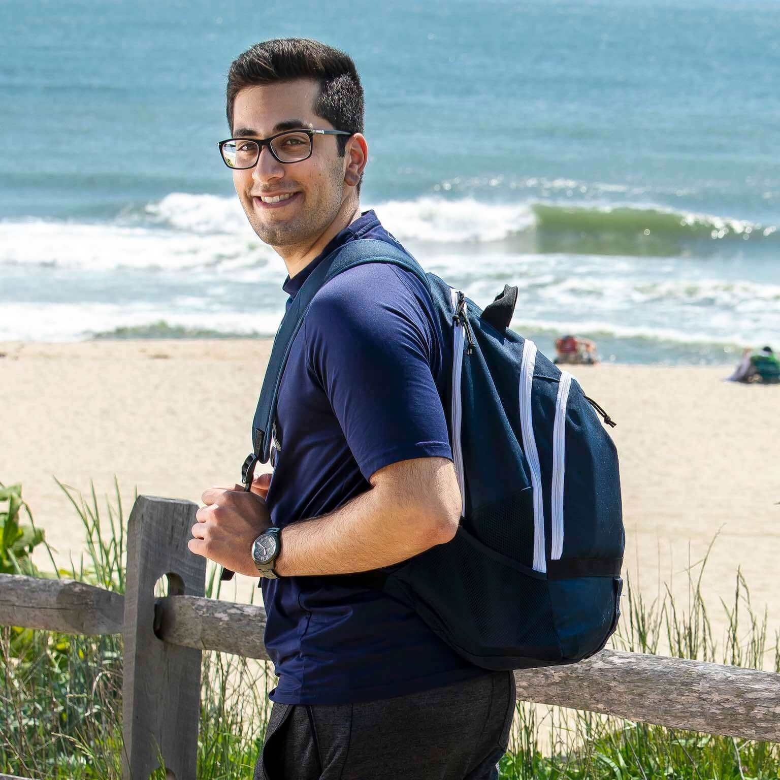 Mehdi Husaini walking by the beach with a backpack.