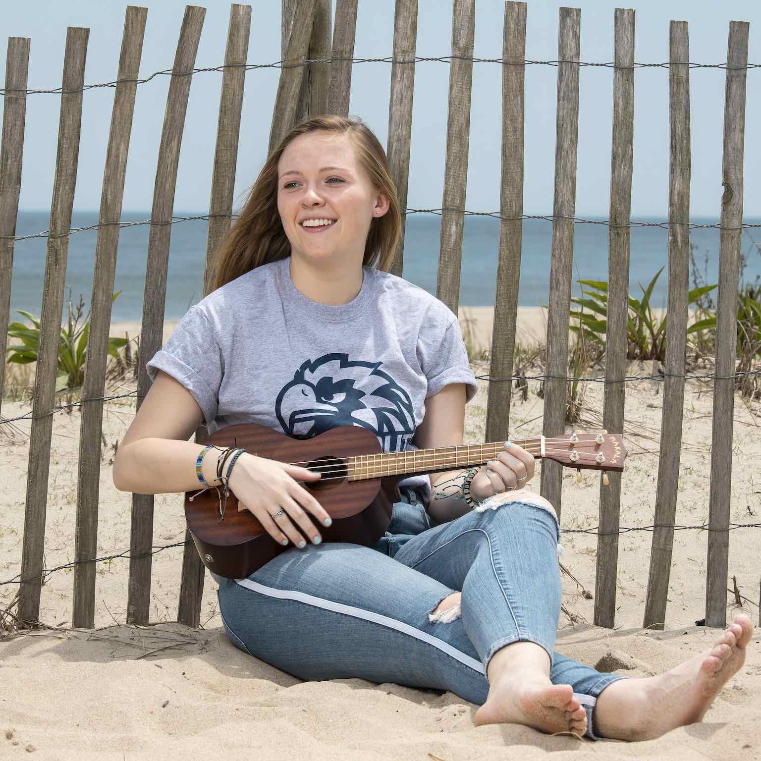 Mikaela McDonough sitting on the beach, playing a ukulele.