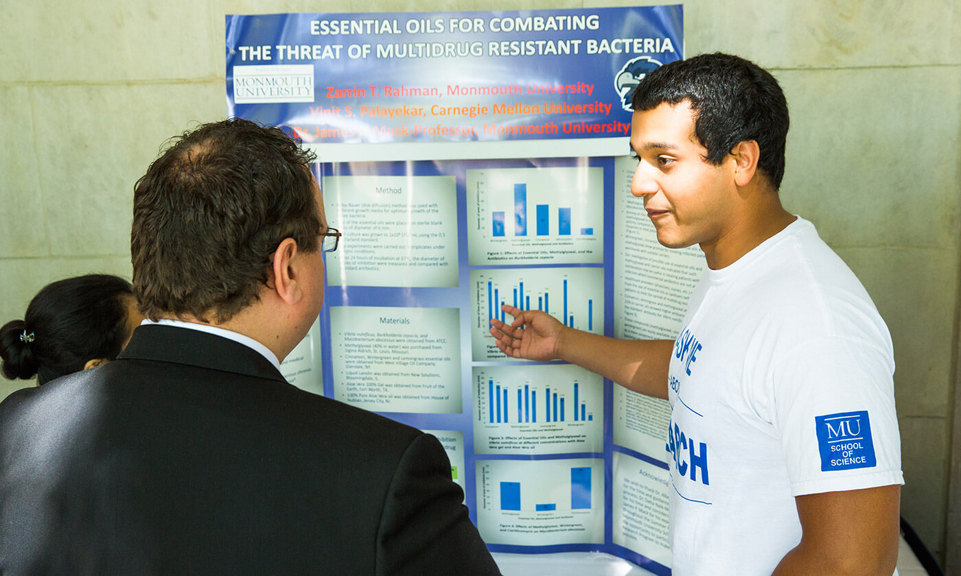 Student presenting charts to professors