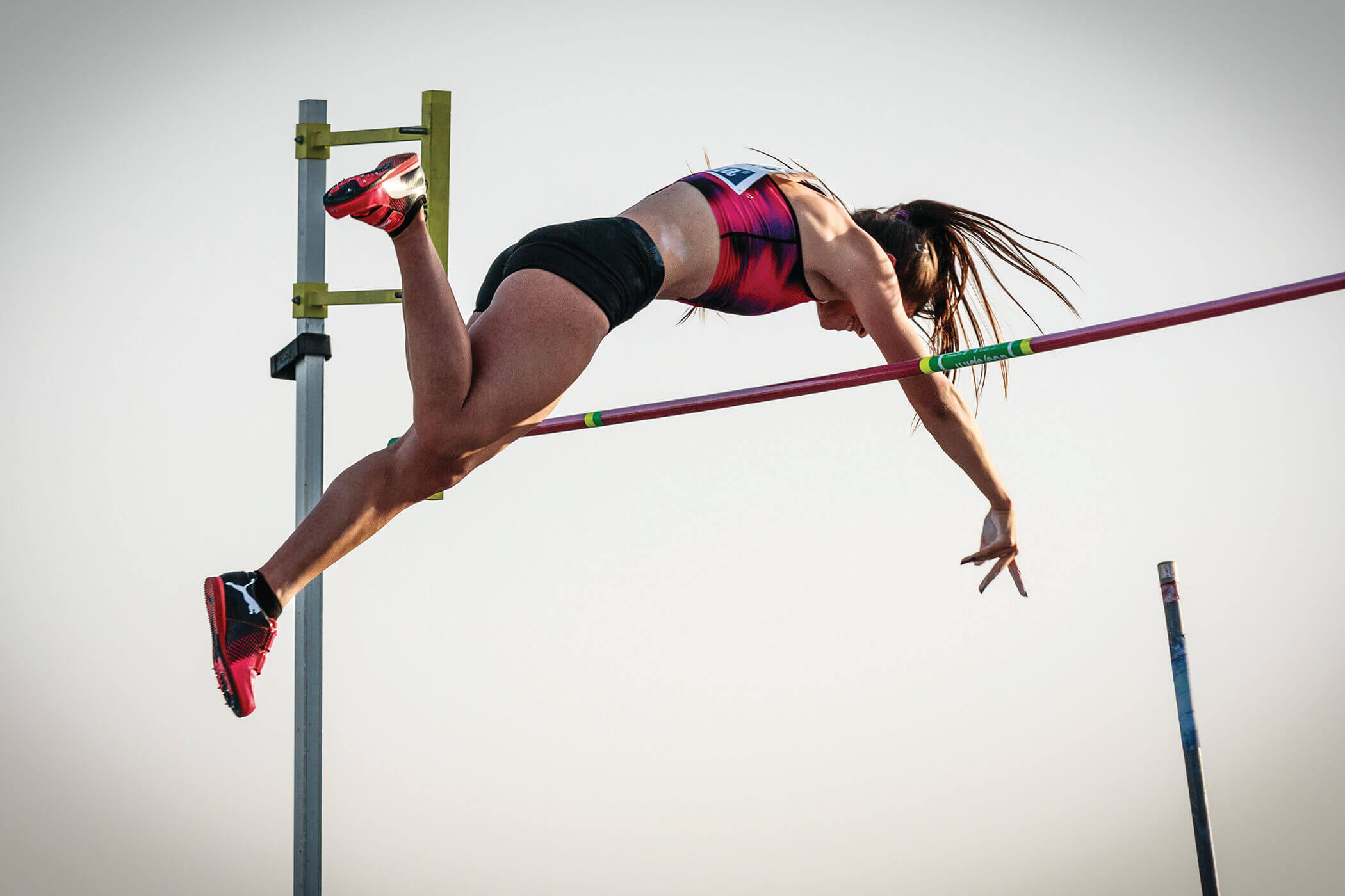 A mid-air pole vaulter arched over the bar she surmounted.