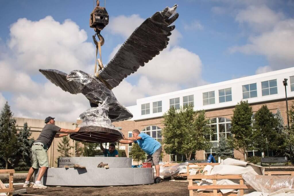 The Hawk at Brockriede Common suspended by a crane, with three workers manuevering the sculpture onto its podium