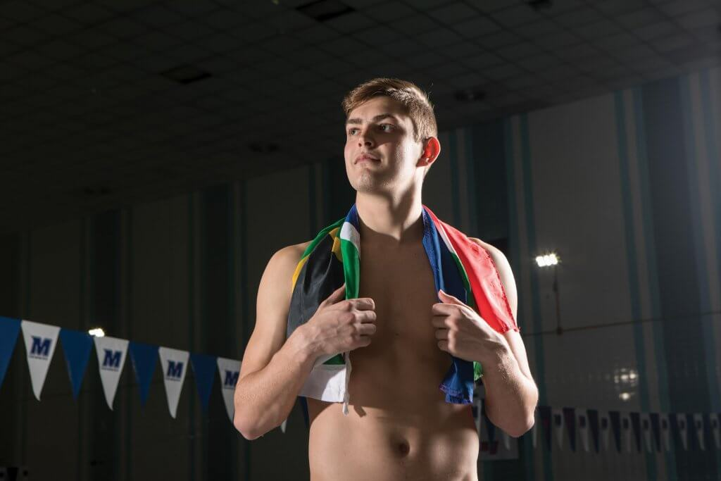 Dylan Barkhuizen standing in Richard E. Steadman Natatorium,adorned with the South African flag around his shoulders