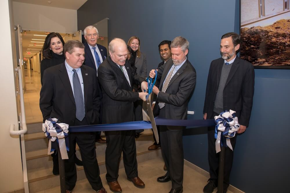 Photo of ribbon cutting; Pictured are School of Science Dean Steven Bachrach and University President Grey Dimenna, Board of Trustees Chair Michael Plodwick (l) and former Board Chair Henry Mercer, III, flank the pair. They are surrounded by (l-r) West Long Branch Mayor Janet Tucci, State Assemblyperson Eric Houghtaling, Superintendent of Higher Education Rochelle Hendricks (partially obscured), State Assemblyperson Joann Downey, and State Senator Vin Gopal.
