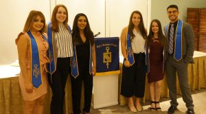 a group of six people wearing blue stoles posing next to each other with a banner in between them.