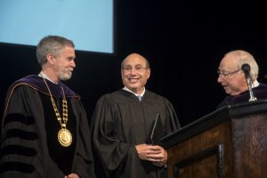 Three men behind a podium, the one in the center is smiliing, all are wearing graduation gowns.