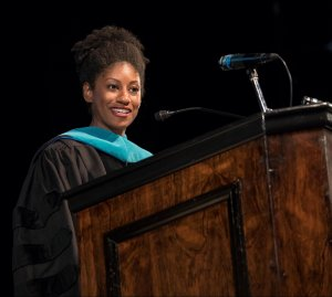 A womean speaking at a podium
