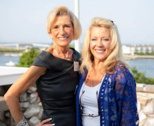 A photo of Carol Stillwell and Valerie Montecalvo posing for a photo standing side by side with a small harbor in the background.