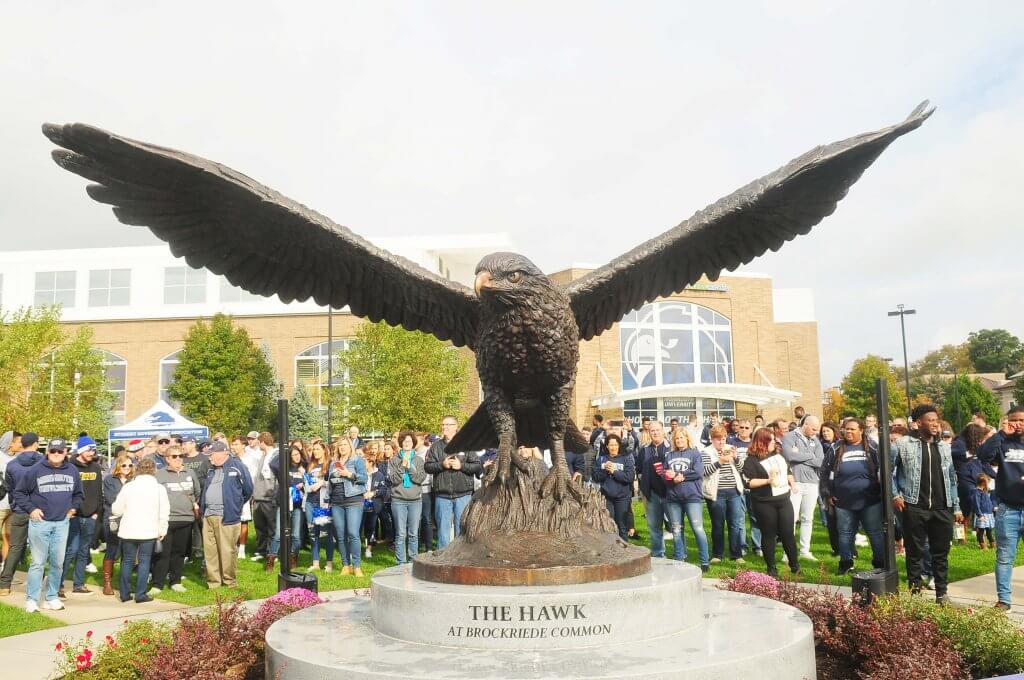 Photo of official dedication ceremony for 22-foot wide bronze sculpture of the Monmouth University Hawk at Brockriede Common held during Homecoming on October 20, 2018.