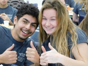1 male and 1 female student holding their thumbs up and smiling