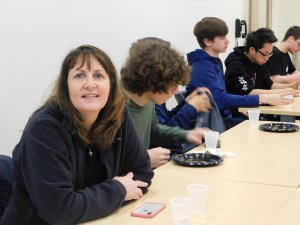 1 woman high school teacher sitting alongside a group of male students eating lunch
