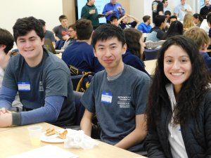 3 students (2 male and 1 female) sitting beside one another, smiling and eating lunch amidst a room of male and female program participants and their advisers