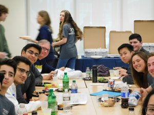 Group of male and female students and teachers eating lunch together and smiling