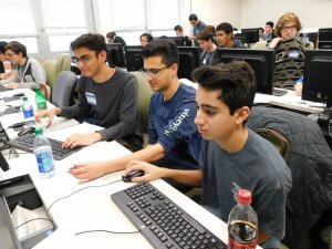 3 male students in front of a group of male and female students working on their programs