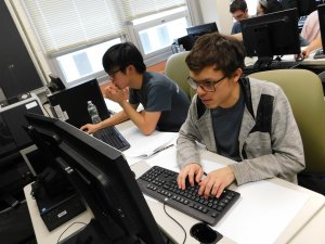 2 male students, 1 typing and 1 using their mouse, working on their computers