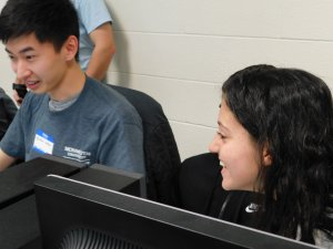 1 male student and 1 female student smiling and having fun at the programming competition