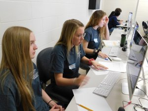 3 female students sitting along side one another with pens and paper on their desk in front of their computers
