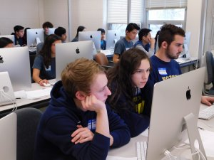 Room full of male and female students working on their programs at the competition with three students, two males and one female in the middle of the two, in the front of the photo