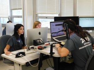 Three female students, 2 facing the camera and 1 facing her computer at the competition